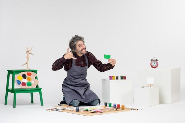 Pintor de frente para o homem segurando um cartão de banco verde sobre fundo branco arte colorida pinturas pinturas dinheiro trabalho de artista