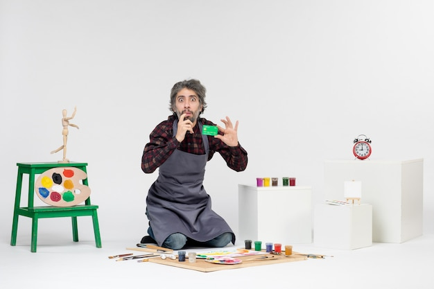 Pintor de frente para o homem segurando um cartão de banco verde sobre fundo branco dinheiro pintando fotos coloridas artista trabalho arte