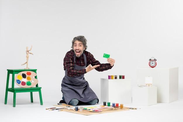 Pintor de frente para o homem segurando um cartão do banco verde no fundo branco arte colorida pintura dinheiro trabalho de artista