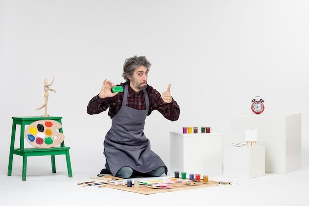 Pintor de frente para o homem segurando um cartão do banco verde no fundo branco pintura da arte cor artista trabalho dinheiro pintura