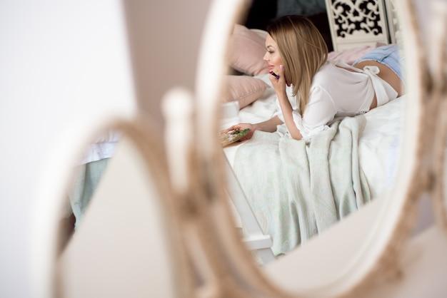 Pintor de menina bonita na cama em seu quarto admira a imagem que ela desenhou
