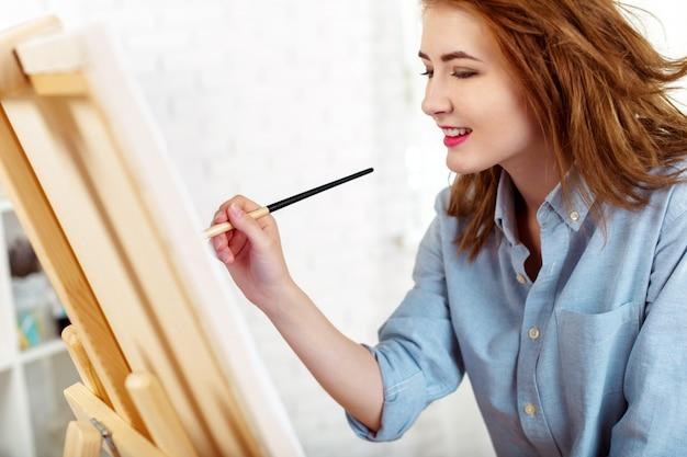Pintor de mulher jovem e bonita no trabalho