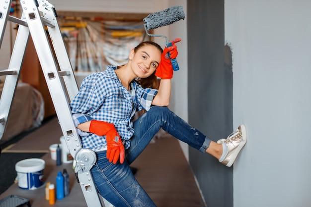 Pintor de paredes feminino em luvas pinta a parede. conserto de casa, mulher rindo fazendo reforma de apartamento, reforma de casa