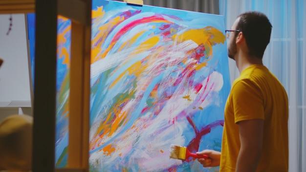 Pintor de sucesso trabalhando em pintura a óleo na oficina de arte.