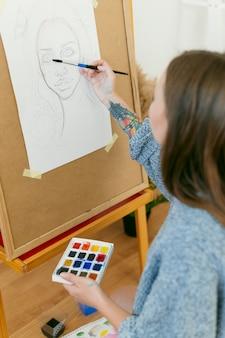 Pintor de visão sobre o ombro desenhando um retrato