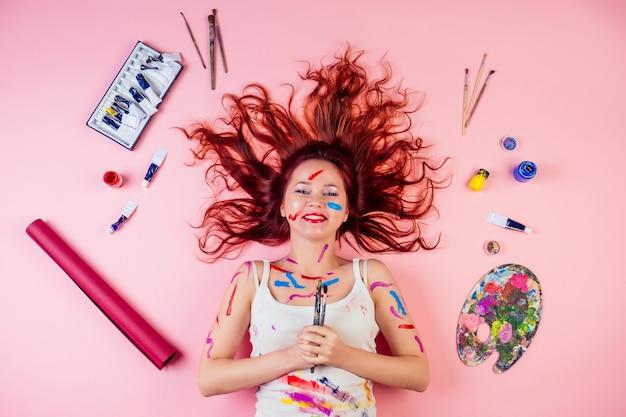 Pintor divertido artista sujo manchas borrão de tinta no rosto deitado no chão ao lado da paleta, tubo de tinta, pincéis em um fundo rosa no estúdio. ideia de musa e inspiração