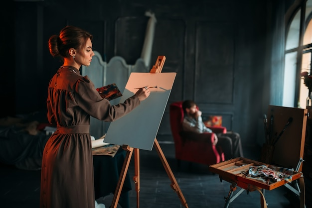Pintor feminino com paleta e pincel na mão pinta o retrato do homem no cavalete no estúdio de arte. tinta a óleo, desenho a pincel