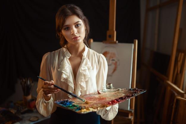 Pintor feminino desenho com paleta de cores e pincel em estúdio.
