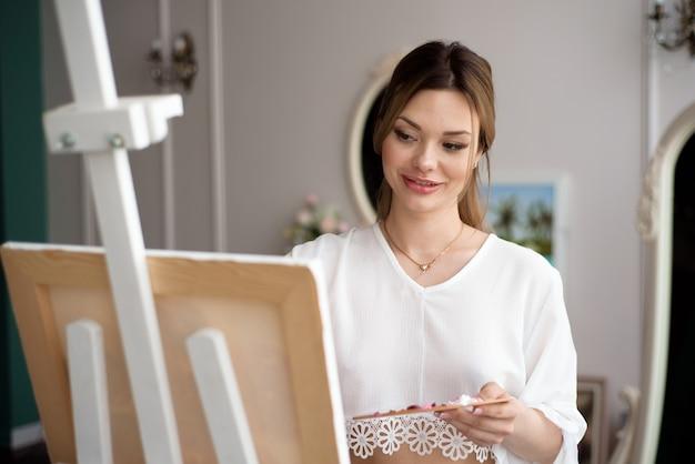 Pintor feminino desenho no estúdio de arte usando cavalete. retrato de uma jovem pintando com tintas a óleo sobre tela branca, vista lateral