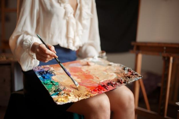 Pintor feminino detém paleta de cores e pincel em estúdio.