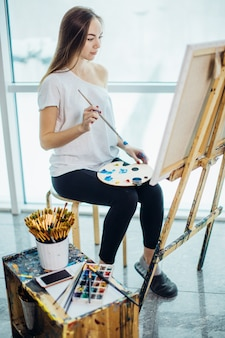Pintor, garota européia desenho mar-scape na lona em sua oficina. conceito de aulas de arte