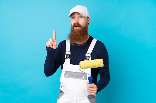 Pintor homem com barba longa sobre parede azul isolada, apontando com o dedo indicador uma ótima idéia