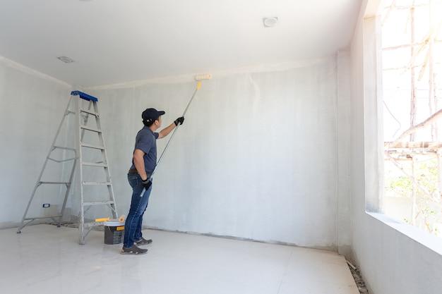 Pintor homem no trabalho com um rolo de pintura na parede