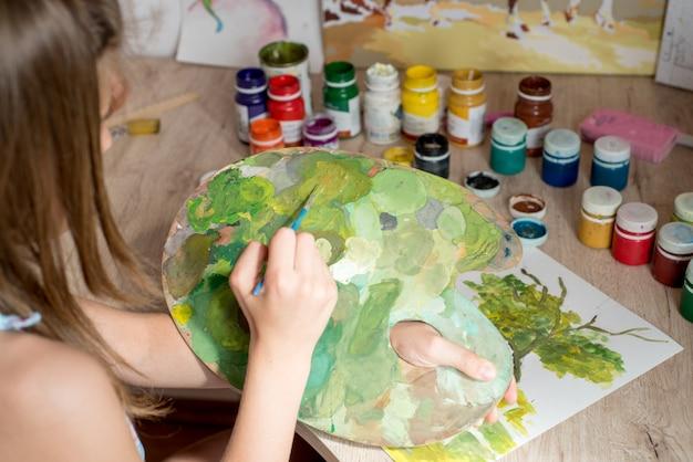 Pintor jovem mulher caucasiana, trabalhando em tela no estúdio de arte