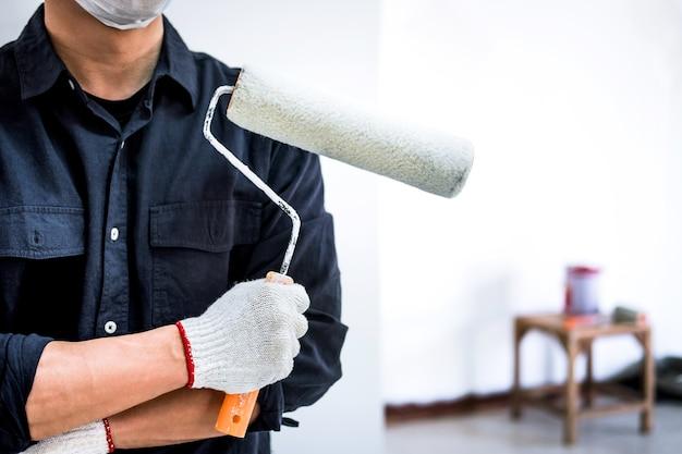 Pintor masculino com braço cruzado segurando o rolo de pintura