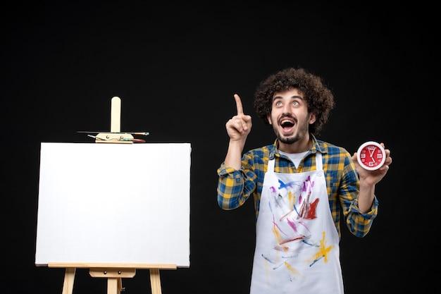 Pintor masculino com cavalete segurando relógios na parede preta