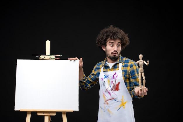 Pintor masculino com cavalete segurando uma figura humana na mesa preta