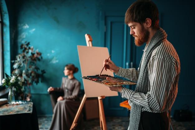 Pintor masculino com paleta e pincel na mão pinta o retrato da mulher no cavalete.