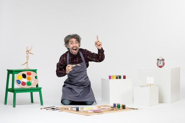 Pintor masculino de frente para dentro da sala com tintas e pincéis para desenhar no fundo branco desenhar arte colorida pintando artistas de imagem