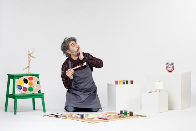 Pintor masculino de frente para dentro da sala com tintas e pincéis para desenhar no fundo branco.