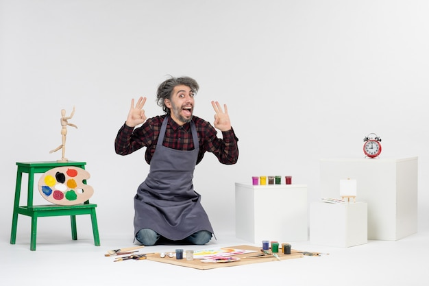 Pintor masculino de frente para dentro de uma sala cheia de tintas e borlas para desenhar no fundo branco.