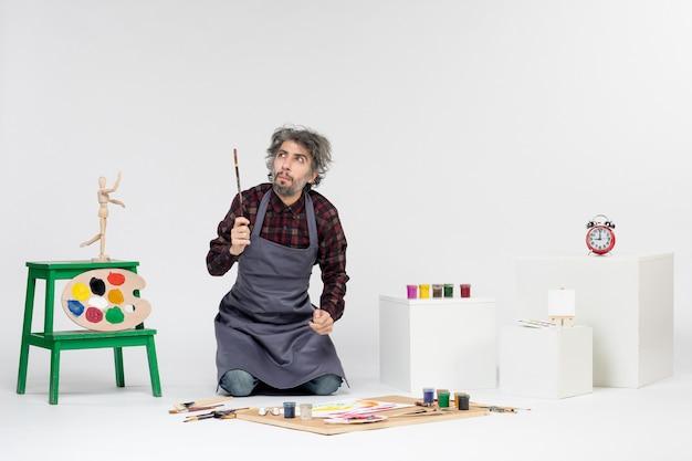 Pintor masculino de vista frontal dentro de uma sala cheia de tintas e borlas para desenhar em um fundo branco.