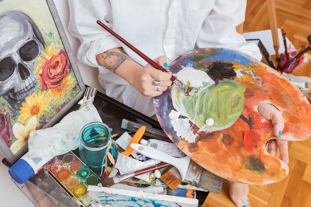Pintor, mergulhando o pincel em tintura na paleta