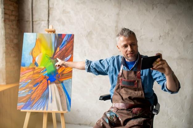 Pintor moderno fazendo selfie ou falando com alguém por videochamada enquanto aponta para uma obra de arte no cavalete no estúdio