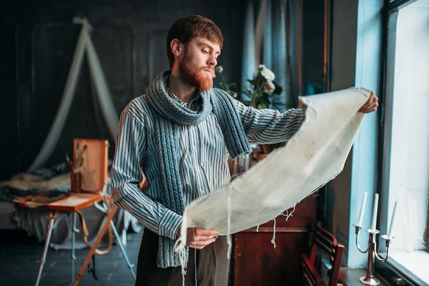 Pintor olhando uma tela contra a janela em um estúdio de arte