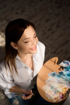Pintor pensativo criativo pinta uma imagem colorida. o close up do processo de pintura na pintura positiva criativa da mulher da oficina da arte pinta em seu estúdio.