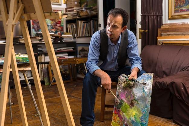 Pintor pensativo sentado em um estúdio segurando uma paleta colorida de artistas e pincel na mão com uma expressão abatida, como se não estivesse feliz com o resultado