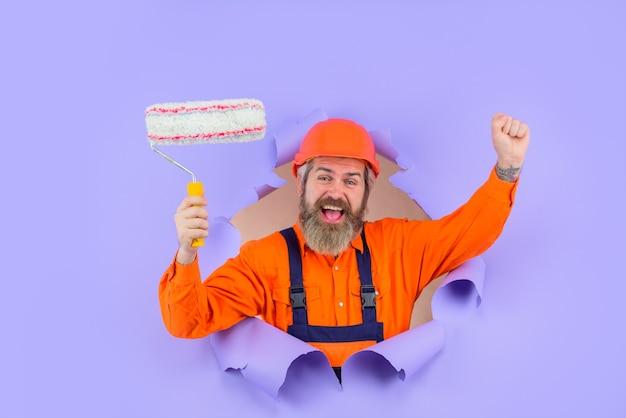 Pintor pintor com rolo de pintura através de orifício no papel trabalhador barbudo feliz com rolo de pintura