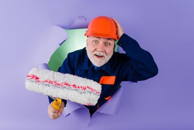 Pintor, pintor com rolo de pintura através do orifício no trabalhador de papel com rolo de pintura profissional