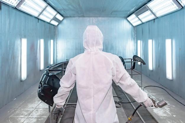 Pintor reparador de automóveis em roupas de trabalho de proteção e respirador pintando o corpo do carro na câmara de pintura