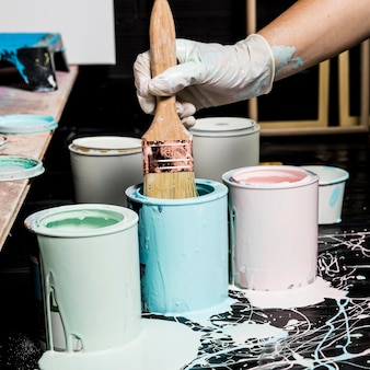 Pintor usando pincel com tinta de latas