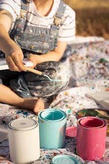 Pintora ao ar livre com latas de tinta