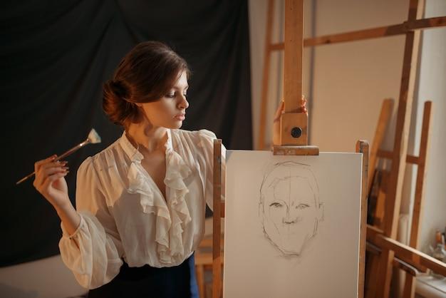 Pintora com pincel em pé contra cavalete