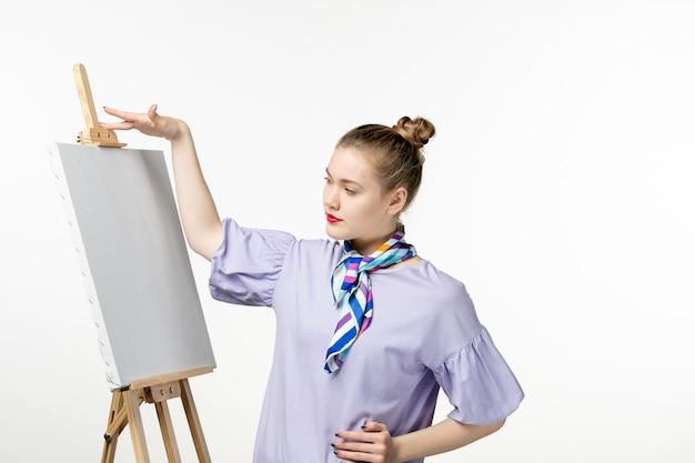 Pintora de frente com cavalete para pintura na parede branca artista fotográfica de mulher desenho exposição de arte