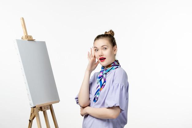 Pintora de frente com cavalete para pintura na parede branca exposição de foto artista desenho de emoção