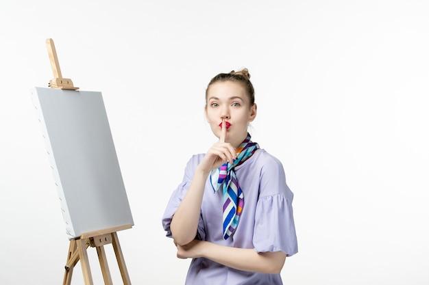 Pintora de frente para pintar com cavalete para pintar no chão branco exposição artista pintura desenho arte em cavalete