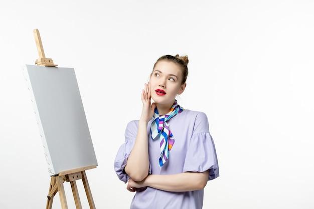 Pintora de frente preparando-se para desenhar no cavalete na parede branca pintura da exposição de arte com borlas do artista