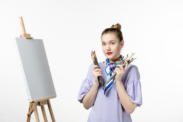 Pintora de frente segurando borlas para desenhar com cavalete na parede branca.