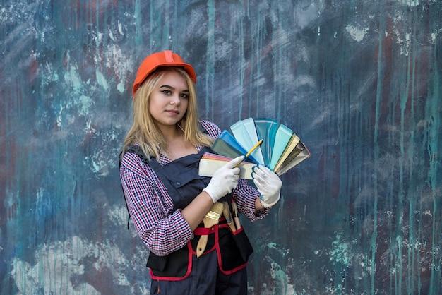 Pintora de uniforme e capacete com quadros de pintura