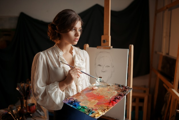 Pintora feminina com paleta de cores e pincel