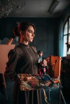 Pintora feminina com pincel e paleta nas mãos