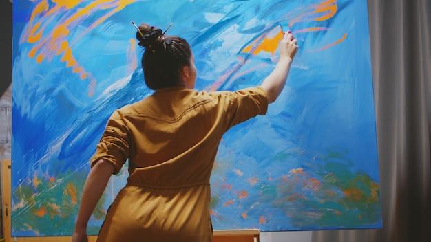 Pintora feminina inovadora usando tinta laranja em uma tela grande.