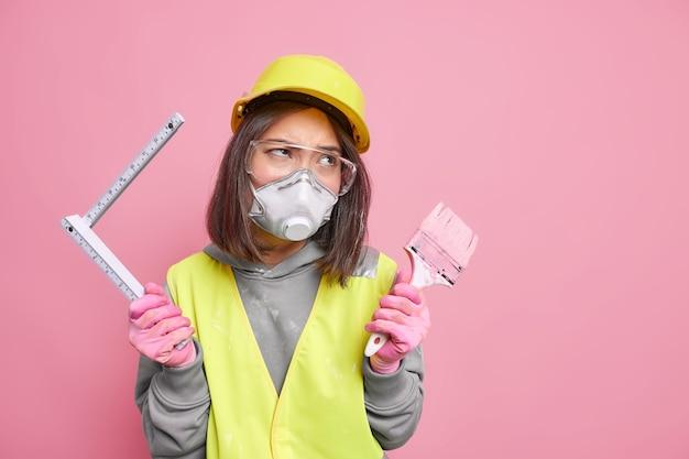 Pintora ou trabalhador de reconstrução segura ferramentas de construção que vão medir as paredes da casa com fita métrica e redecorar algo no apartamento. conceito de casa e reparo