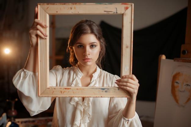 Pintora segurando moldura de madeira na frente do rosto em estúdio