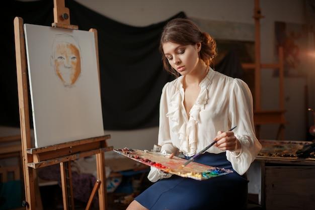 Pintora segurando paleta de cores e pincel