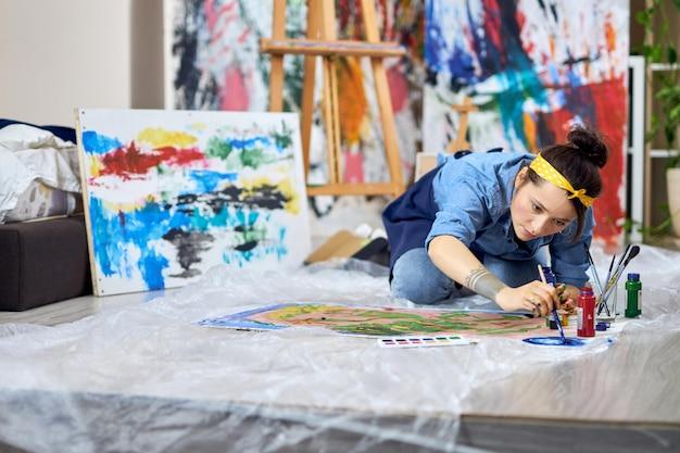 Pintora talentosa com avental escolhendo a cor da tinta segurando o pincel enquanto trabalha na pintura